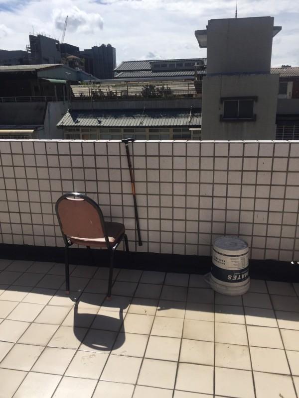老翁搬椅子以便攀上陽台圍牆。(記者劉慶侯翻攝)