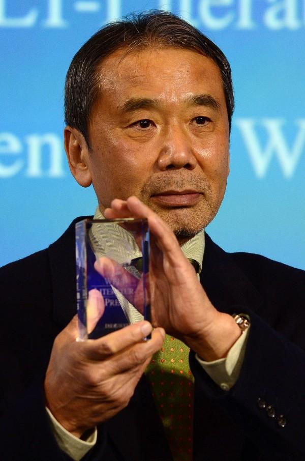 日本文豪村上春樹近來多次叩關諾貝爾文學獎,卻屢戰屢敗。圖為他2014年獲得德國《世界報》文學獎後,手持獎盃接受媒體拍照。(法新社)