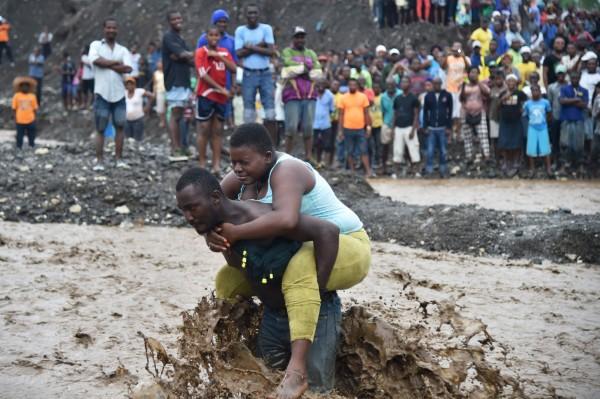 颶風馬修(Matthew)近日肆虐加勒比海一帶,已在海地等國造成嚴重災情。圖為海地民眾冒險涉水。(法新社)