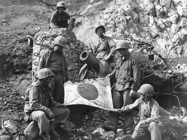 身為太平洋勝利者的美軍,在清理戰場時,時常將日軍遺物作為紀念品帶走。圖為硫磺島戰役時,美軍拾獲「日之丸旗」。(圖擷自《維基百科》)