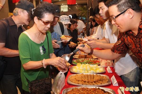 現場也準備了印尼沙嗲、娘惹糕等異國美食,讓民眾大排長龍,準備大快朵頤。(記者鍾泓良攝)