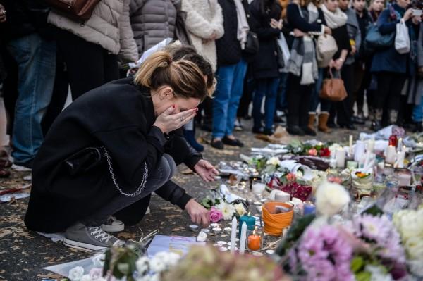 發生在去年11月13日至14日凌晨的巴黎恐攻,共造成130位民眾無辜喪命,現在卻傳出比利時警察在事前錯失13次機會逮捕主嫌。圖為罹難者親友在恐攻現場哀悼死者。(歐新社)