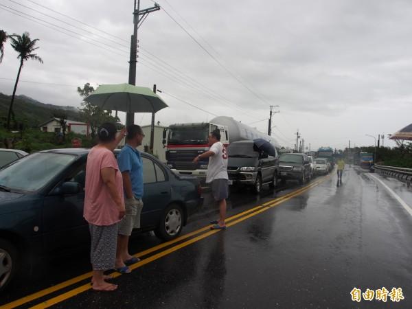 從清晨到上午都在封路點等通車的民眾,趁著雨勢稍緩,走出車子聊天打發時間。(記者王秀亭攝)
