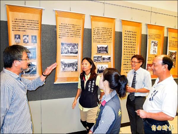 策展人藍博洲(左)向來賓解說日治台灣歷史圖文的珍貴可看性。(記者王俊忠攝)