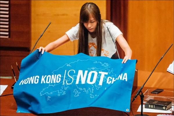 「青年新政」議員當選人游蕙禎在宣誓時帶著寫有「HONG KONG IS NOT CHINA」字樣的布條上台。(彭博)