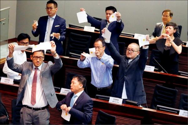 香港第六屆立法會議員十二日宣誓就任,三名本土派、非建制派議員因在誓詞中增加「香港民族」、「爭取真普選」等內容,被判定宣誓無效,導致三人無法在下午的主席選舉中投票,泛民主派議員為此撕毀選票、離場抗議。(路透)