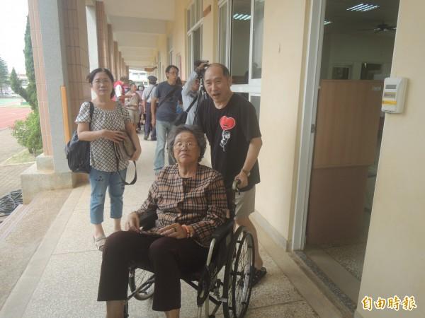 民眾推輪椅送老人家投票,行使神聖的權利。(記者劉禹慶攝)