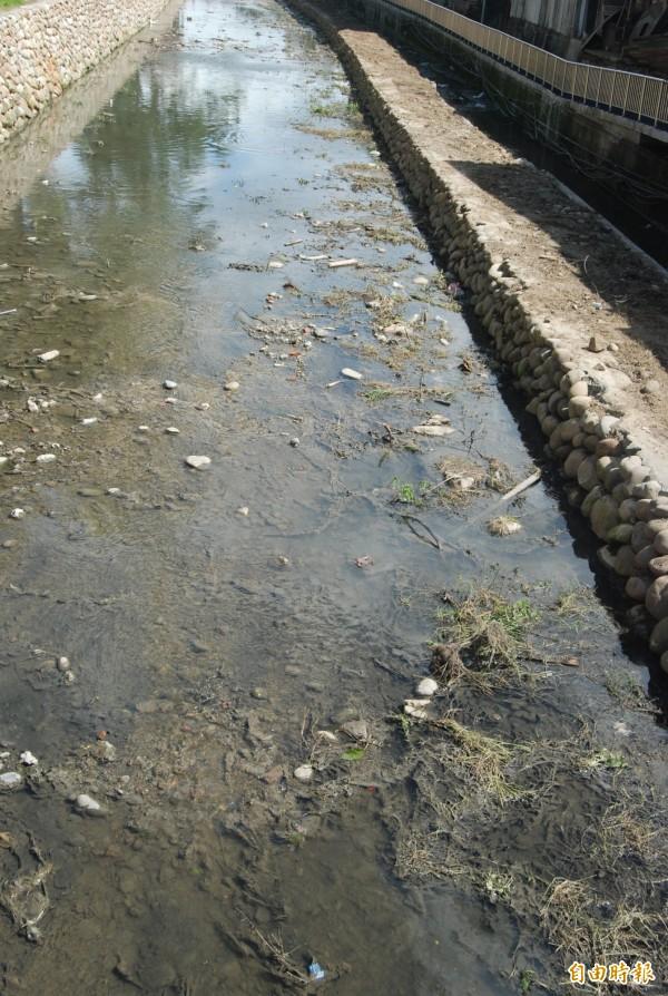 新北市水利局原定八月底完成鹿角溪下游中州街至味王街的整治工程,未料至今河道上還堆滿泥沙與垃圾,嚴重影響排水。(記者張安蕎攝)