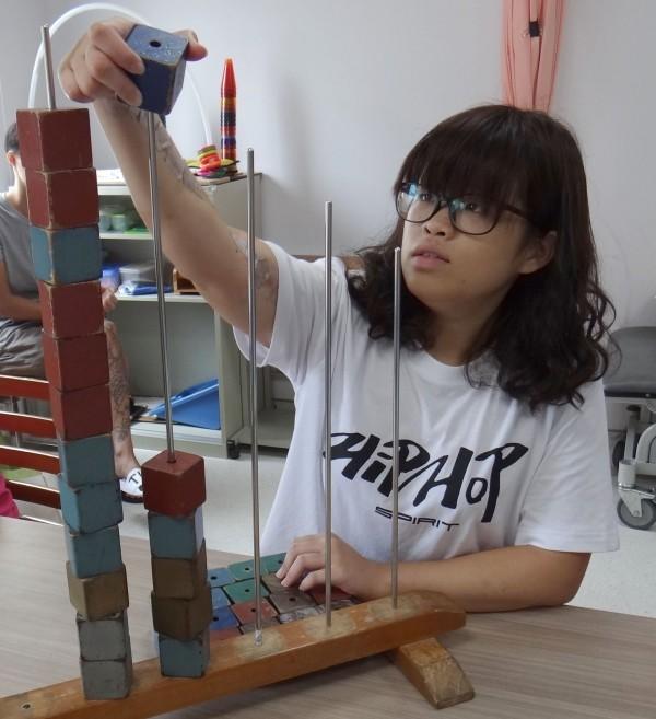 毛藝諼在奇美醫學中心復健治療團隊協助之下,逐漸恢復手部功能。(奇美醫學中心提供)