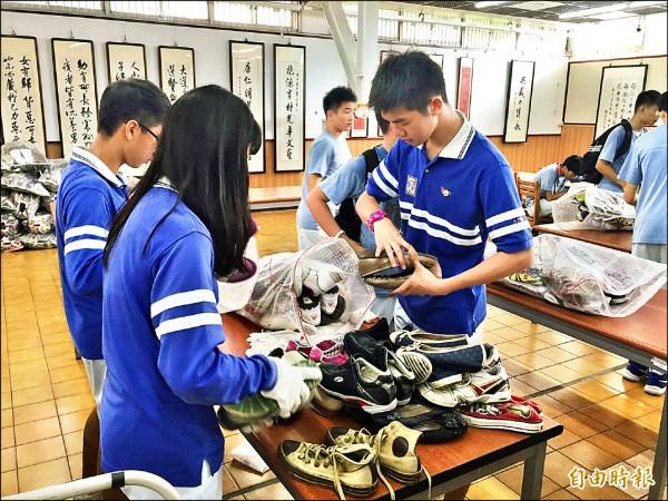 志工們一一整理蒐集來的鞋子。 (記者何宗翰攝)