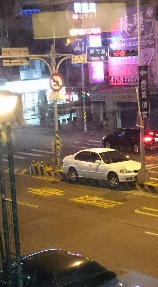 白色轎車騰空卡在馬路分隔島上,前後還卡著燈柱,讓人好奇到底是怎麼「停」上去的?(圖擷取自爆料公社臉書粉絲專頁)