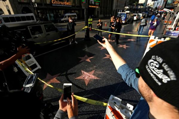 川普被嵌在好萊塢星光大道的「川普星星」,昨日遭到一名自稱是傑米的男子持鐵鎚敲爆,整顆大星成了一片片殘破不堪的瓦塊。(路透)