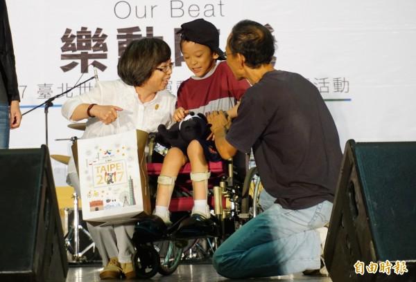 腦麻學童林易為台北世大運創作主題曲,世大運執行長蘇麗瓊特別上台贈送禮物致意。(記者蔡淑媛攝)
