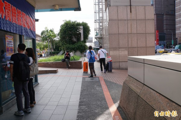 國光客運派人到西站原址,看到像遊客的人就會主動上前告知搭車地點已經更換。(記者張凱翔攝)