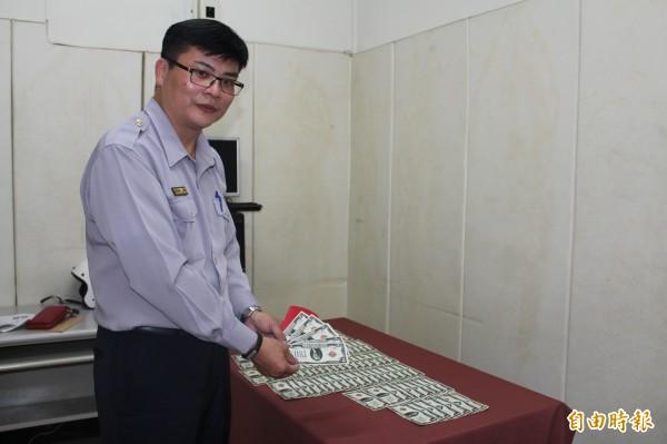 竹北分局新工所所長吳榮財關心深夜路旁聊天的男女,意外查獲圖中的「鉅額」假美鈔。(記者黃美珠攝)
