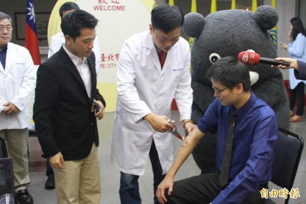 中醫師示範拔罐,拿著器具真空吸附皮膚。(記者郭逸攝)