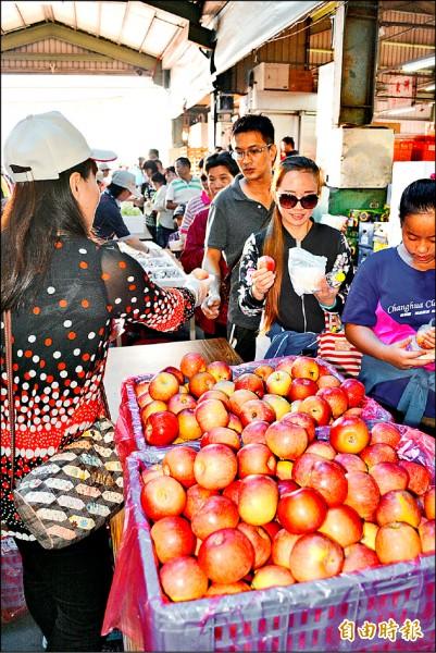 彰化果菜市場備有上萬台斤水果,吸引爆滿的大人小孩排隊搶吃。(記者湯世名攝)