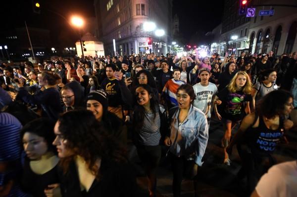 加州灣區爆發反川普示威,示威者走上街頭高呼口號。(路透)