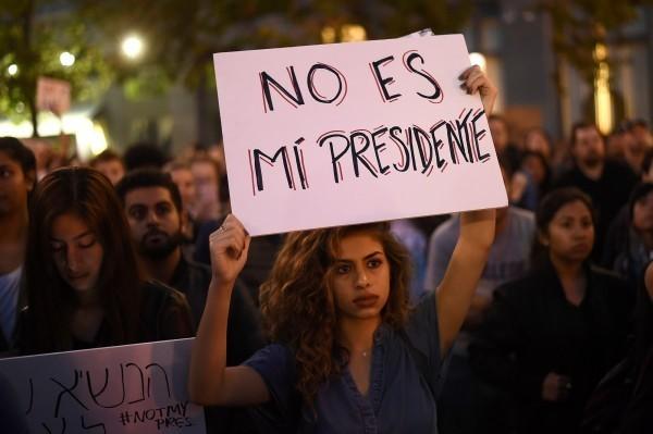 加州爆發反川普抗議遊行,民眾高舉「他不是我的總統」的西語海報。(路透)