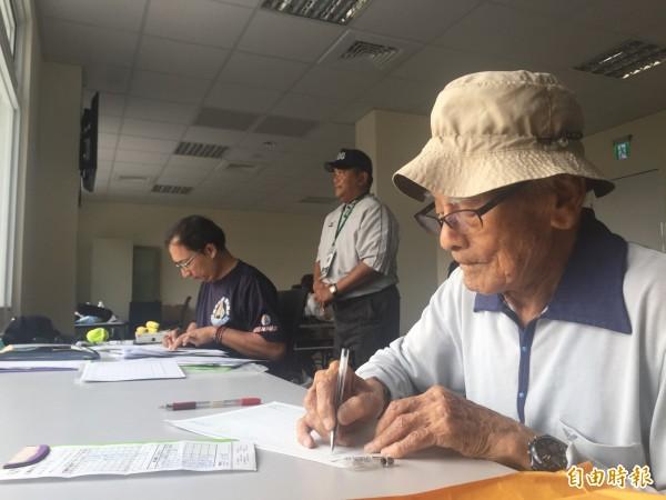已經高齡92歲的吳富興(右),對棒球的熱情一生不滅,今天仍端坐場邊記錄中信盃少棒賽。(記者羅欣貞攝)