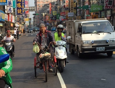 新竹市警二分局關東橋派出所警員郭珀杉騎機車「助推」三輪車,護送老翁安全通過路口。(圖由呂建宏提供)