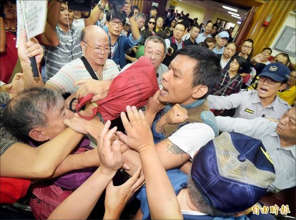 日本食品輸台公聽會昨在台北等地續辦,場內爆發流血衝突,警方在混亂中試圖架開兩派人馬,仍有五位民眾受傷就醫。民進黨立委姚文智痛批國民黨已淪為黑道。(記者黃耀徵攝)