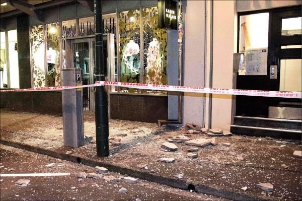 圖為紐國首都威靈頓市區的人行道散落一地被強震震裂的建物瓦礫與玻璃。(法新社)