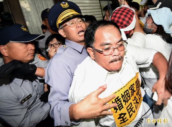 部分現場反同婚群眾下午兩點多,欲翻過立法院側門進入立法院,與警方爆發衝突。(記者朱沛雄攝)