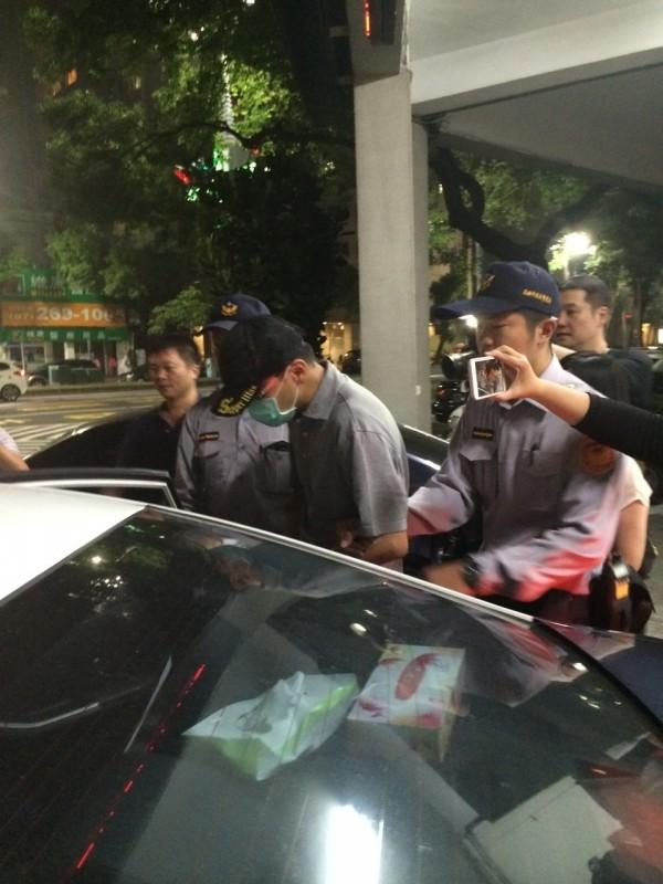 醫美診所院長倪宗亨(中戴黑帽者)接受警方偵訊時,仍堅稱沒喝酒、沒超速。(記者洪定宏翻攝)
