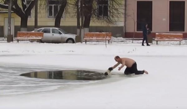 戰鬥民族為了救援掉進冰池裡的狗狗,不畏伸手讓牠猛咬。(圖擷自YouTube)