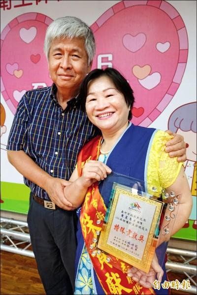 乳癌病友黃麗月在先生的陪伴領取衛生保健志工特殊貢獻獎,並呼籲病友不要放棄希望,家人的支持也重要。(記者蔡淑媛攝)