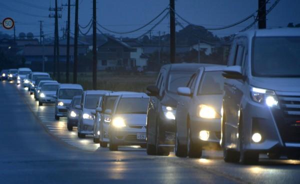 日本東北部地區發生強震後,當地街頭出現大批車潮。(路透)