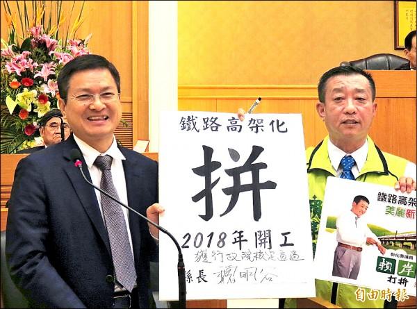 彰化縣議員賴岸璋(右) 拿出承諾書,要縣長魏明谷(左)簽名、並承諾彰化市鐵路高架計畫必須在2018年之前開工。(記者林良哲攝)