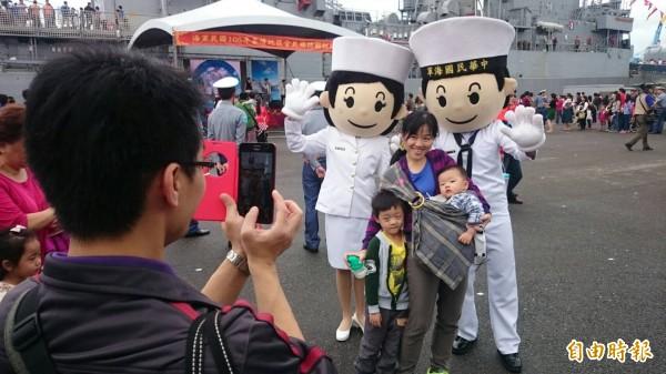 國防部海軍司令部26日在基隆港威海營區舉辦「全民國防艦艇開放參觀」活動,民眾與可愛的海軍公仔合照。(記者俞肇福攝)