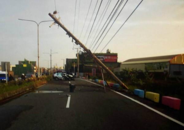 休旅車撞斷電線桿後橫躺路中央,電線桿僅靠電纜線支撐,嚴重傾斜。(記者湯世名翻攝)