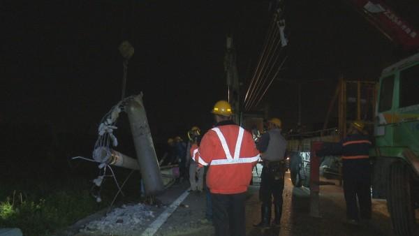電線桿被休旅車撞斷後,僅靠電纜線支撐,當地大停電,台電人員緊急搶修。(記者湯世名翻攝)