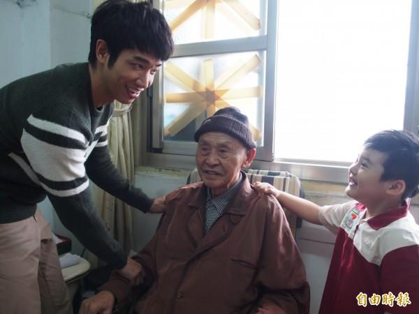劉以豪(左)與小粉絲郭政諺(右)送餐時,還貼心地為呂爺爺按摩。(記者王秀亭攝)