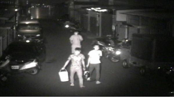 監視器拍攝到暴力討債集團,提著桶子潑尿與潑漆討債。(記者張瑞楨翻攝)