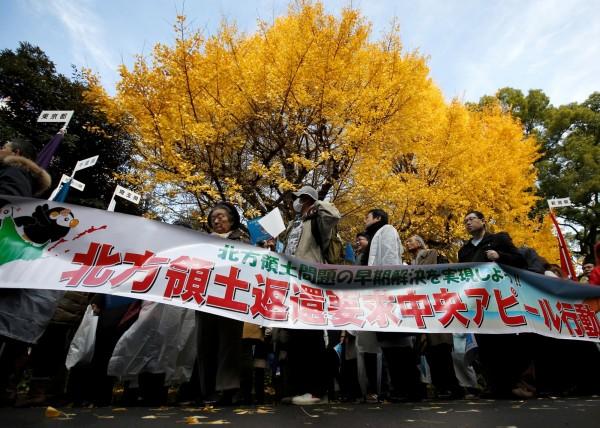 要求俄羅斯歸還北方四島的抗議人士1日在日本東京遊行時經過一棵樹葉已變黃的銀杏樹。(路透)