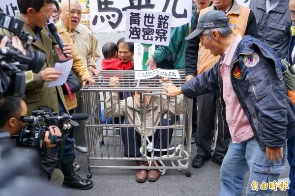 曾經有「抗議天王」之稱的柯賜海(中抱紅衣童者),今天也出現在北檢外抗議馬英九的人潮中。(記者黃欣柏攝)