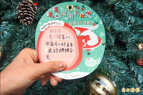 小朋友在卡片上寫下想要耶誕禮物的願望,希望透過戒指全家能夠團圓。(記者林孟婷攝)