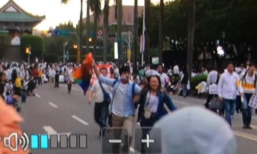 楊男拿著彩虹旗在反同集會中飛奔吶喊。(記者王冠仁翻攝)