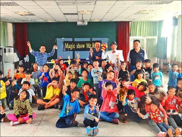 藏谷和夫(後排右二)雖與永安國小學生語言不通,靠著肢體語言及魔術,學生們度過快樂的四十分鐘。(永安國小提供)