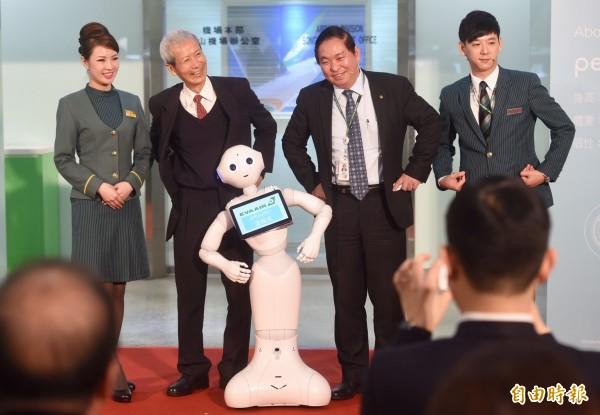 長榮航空宣布引進人形機器人Pepper加入服務行列,台北航空站主任朱耀光、長榮航空機場本部副總陳有玉7日在台北松山機場國際線,歡迎這位活力十足的生力軍,並跟Pepper大玩三連拍。(記者簡榮豐攝)