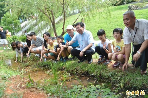 桃園市日前舉辦的手護老街溪活動,大人、小孩一起種下萍蓬草。(資料照,記者李容萍攝)