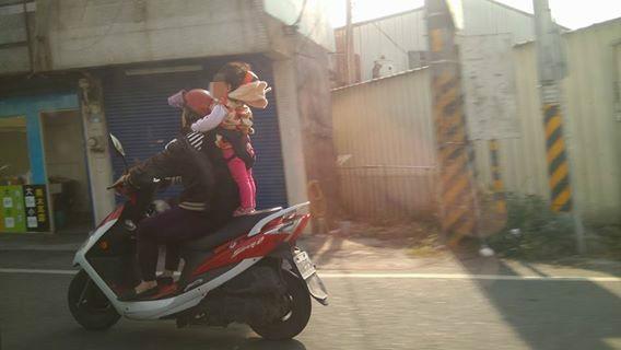 彰化一名婦人在路上加速奔馳,後方小女孩就站立在後座,被網友拍下投訴至彰化交警網頁。(圖擷自爆料公社)