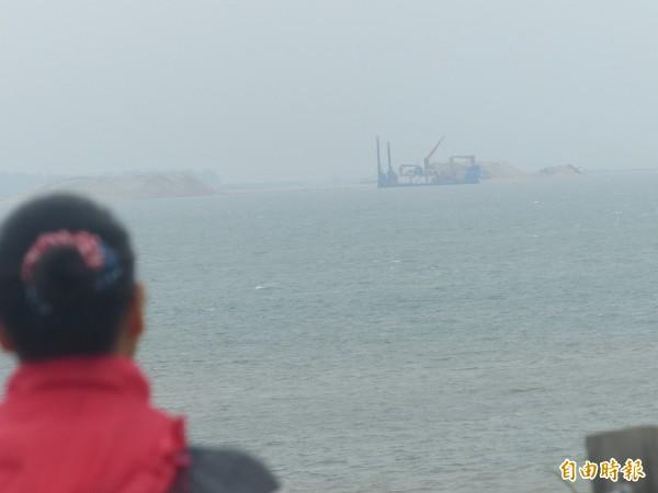 金門北山紅土斷崖土方嚴重崩落,遊客用肉眼可看見中國船在「中線」一帶抽砂景象。(資料照,記者吳正庭攝)