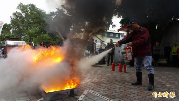 關山消防分隊指導參與演練的民眾正確的滅火器使用方法。(記者王秀亭攝)