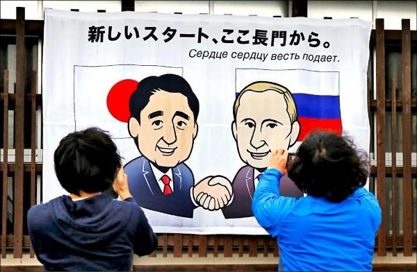 日本山口縣長門市為迎接十五日召開的日俄元首會談,街上掛滿首相安倍晉三與俄羅斯總統普廷握手的漫畫海報,海報上以日俄文寫著「新的起點由長門開始」。(路透)