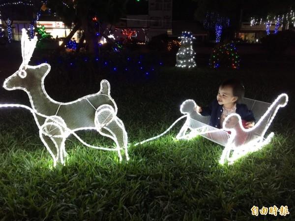小朋友坐燈光雪橇,笑的合不攏嘴。(記者詹士弘攝)